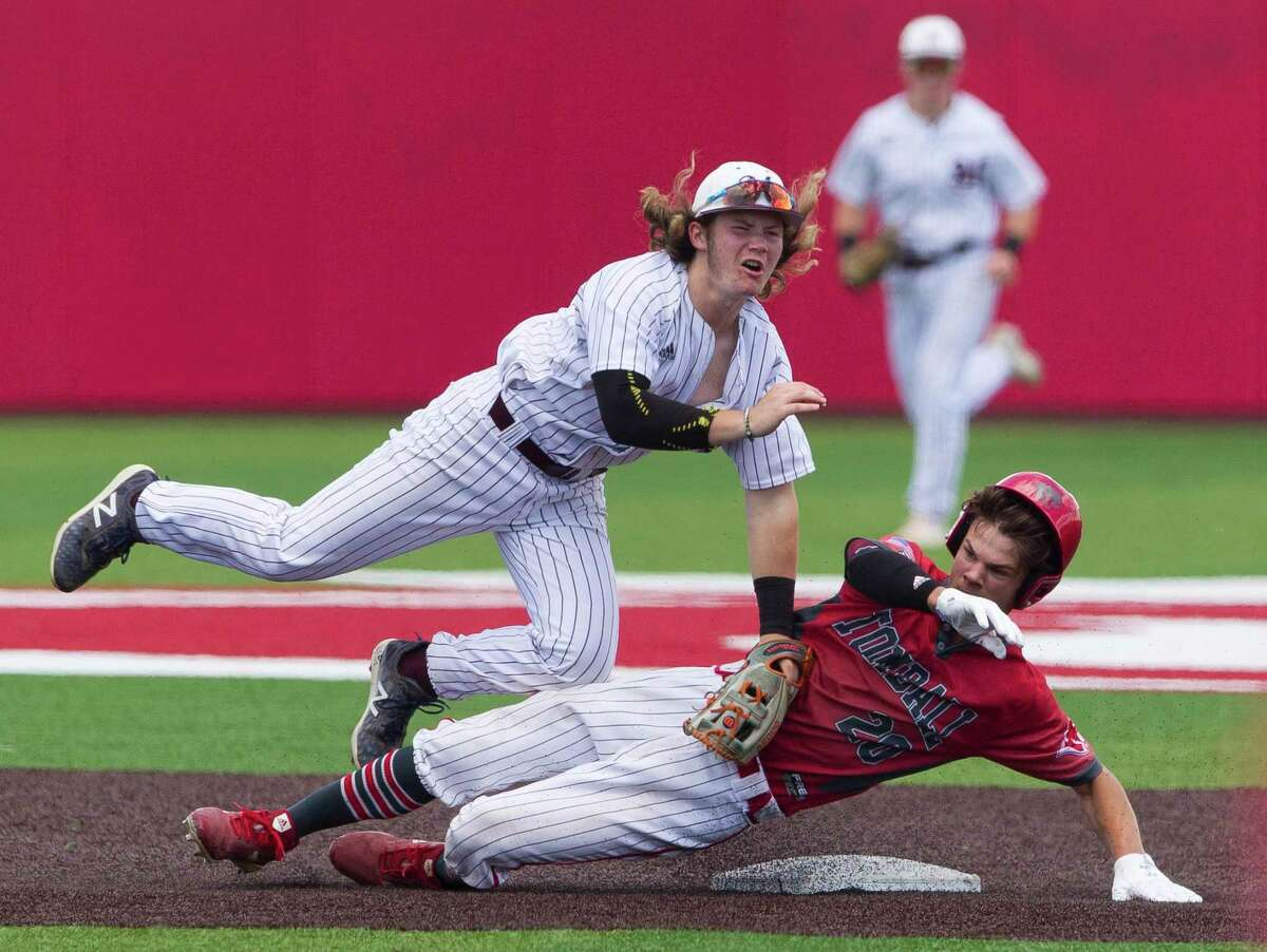 Jake Johnson #20 of Tomball is called out after a hard slide into Magnolia second baseman Caleb Clines (4) in the seventh inning of Game 3 during a Region III-5A bi-district high school baseball playoff game, Saturday, May 4, 2019, in Crosby.