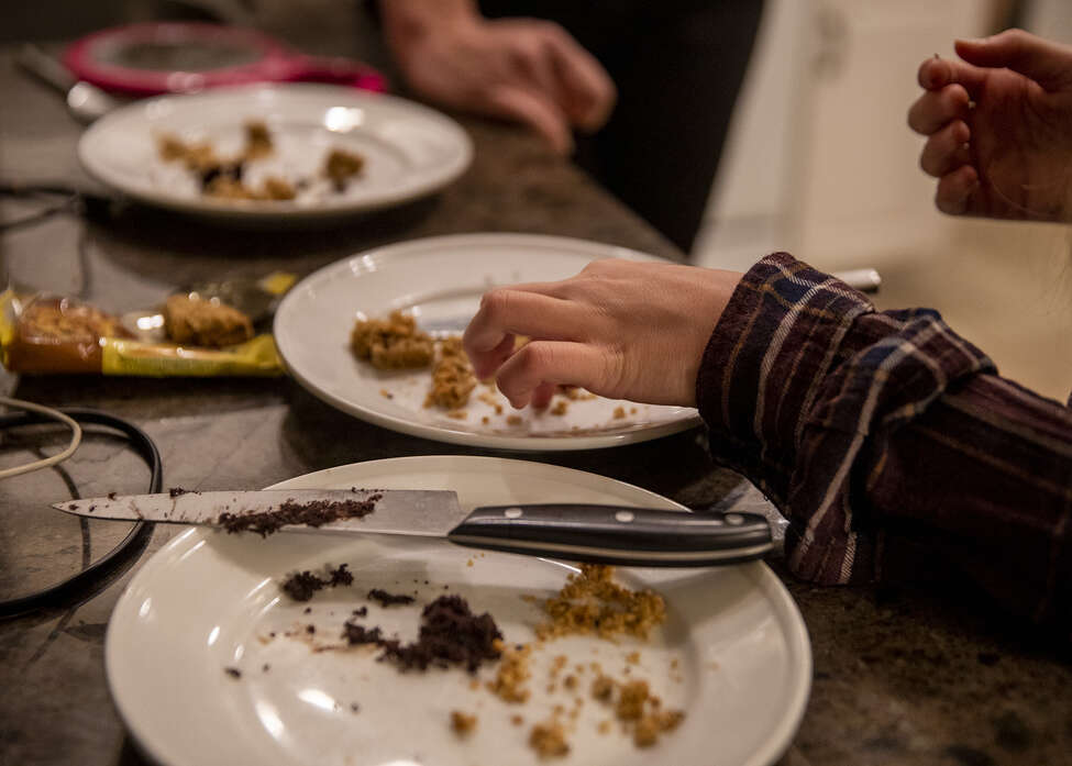 Kate Schonwald, 12, eats crumbs of a breakfast biscuit during her second session with occupational therapist Karen Dilfer who specializes in food therapy in Schonwald's Evanston, Ill. home on Monday, Dec. 2, 2019. (Camille Fine/Chicago Tribune/TNS)