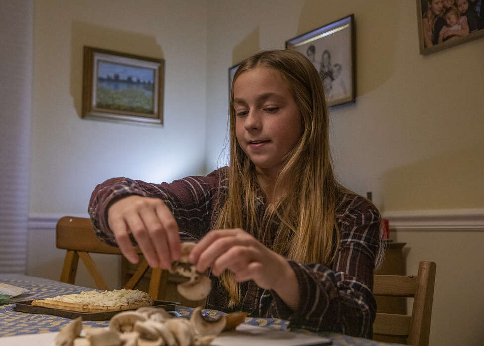 Kate Schonwald, 12, tops a pizza for dinner while working with occupational therapist Karen Dilfer, who specializes in food, in Schonwald's Evanston, Ill. home on Monday, Dec. 2, 2019. (Camille Fine/Chicago Tribune/TNS)