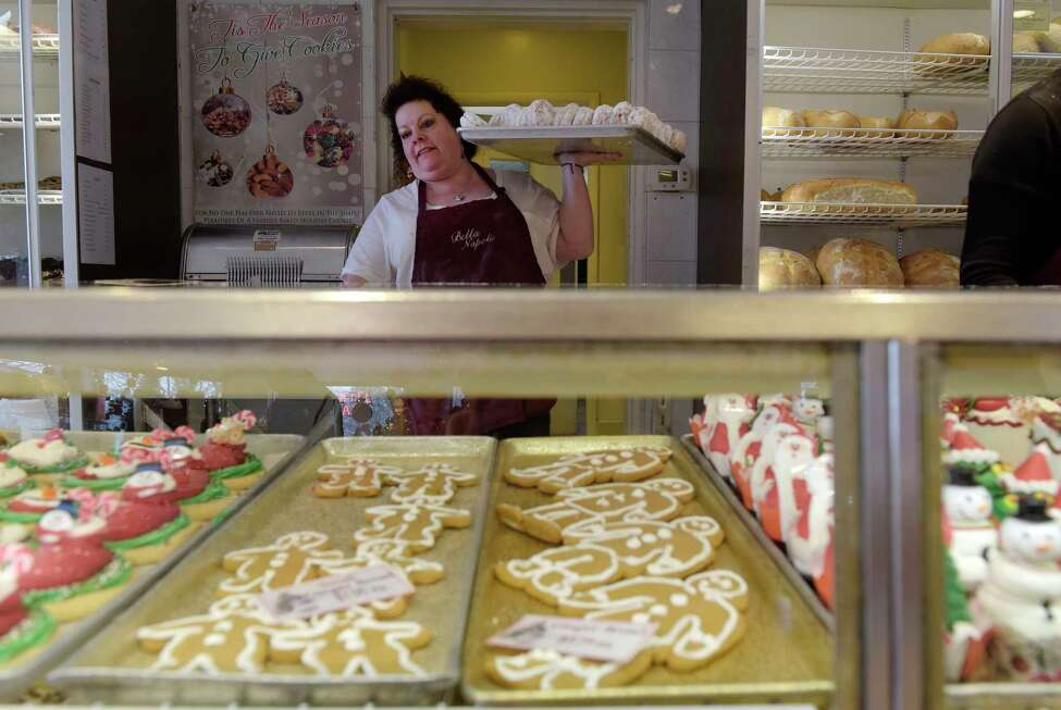 Stacey Claus carries a tray of doughnuts out to the front case at Bella Napoli during a brief pause in customers on Tuesday, Dec. 12, 2017, in Latham, N.Y. (Paul Buckowski / Times Union)