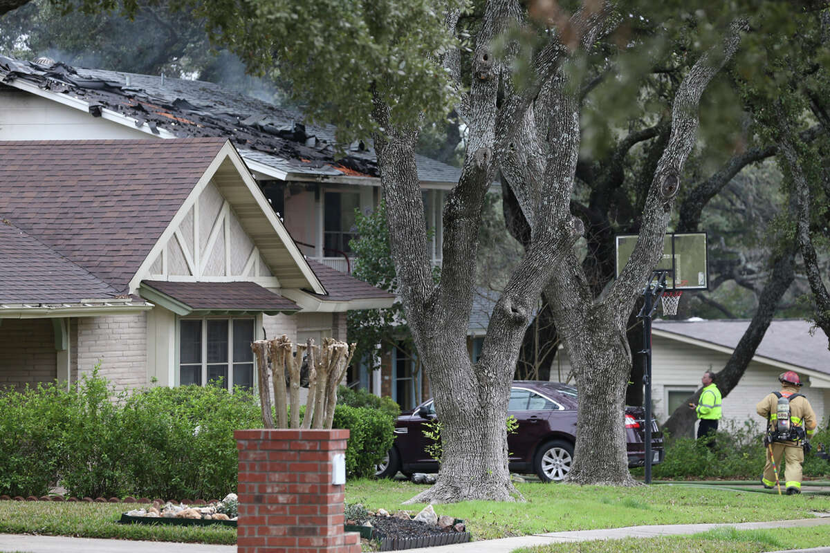Fire damage is seen on the roof of a house on the 3400 block of Stonehaven Road, Wednesday, Feb. 19, 2020. According to San Antonio Police Chief William McManus, a man 29-year-old male barricaded himself in the house after they responded to a vehicle fire at the scene. His body was later found on the second floor.