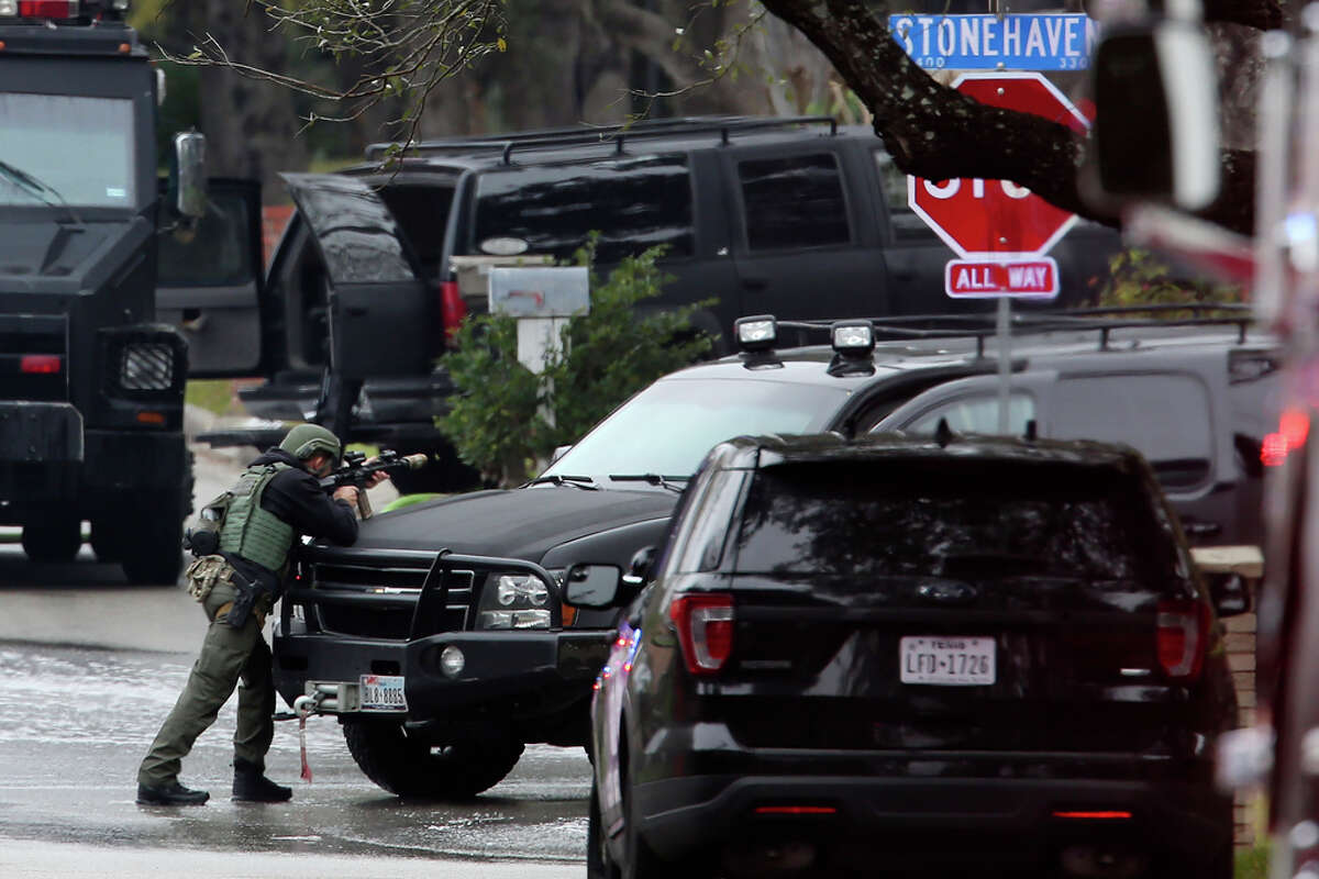 A SWAT member stands ready outside a of a house on the 3400 block of Stonehaven Road, Wednesday, Feb. 19, 2020. According to San Antonio Police Chief William McManus, a man 29-year-old male barricaded himself in the house after they responded to a vehicle fire at the scene. His body was later found on the second floor.