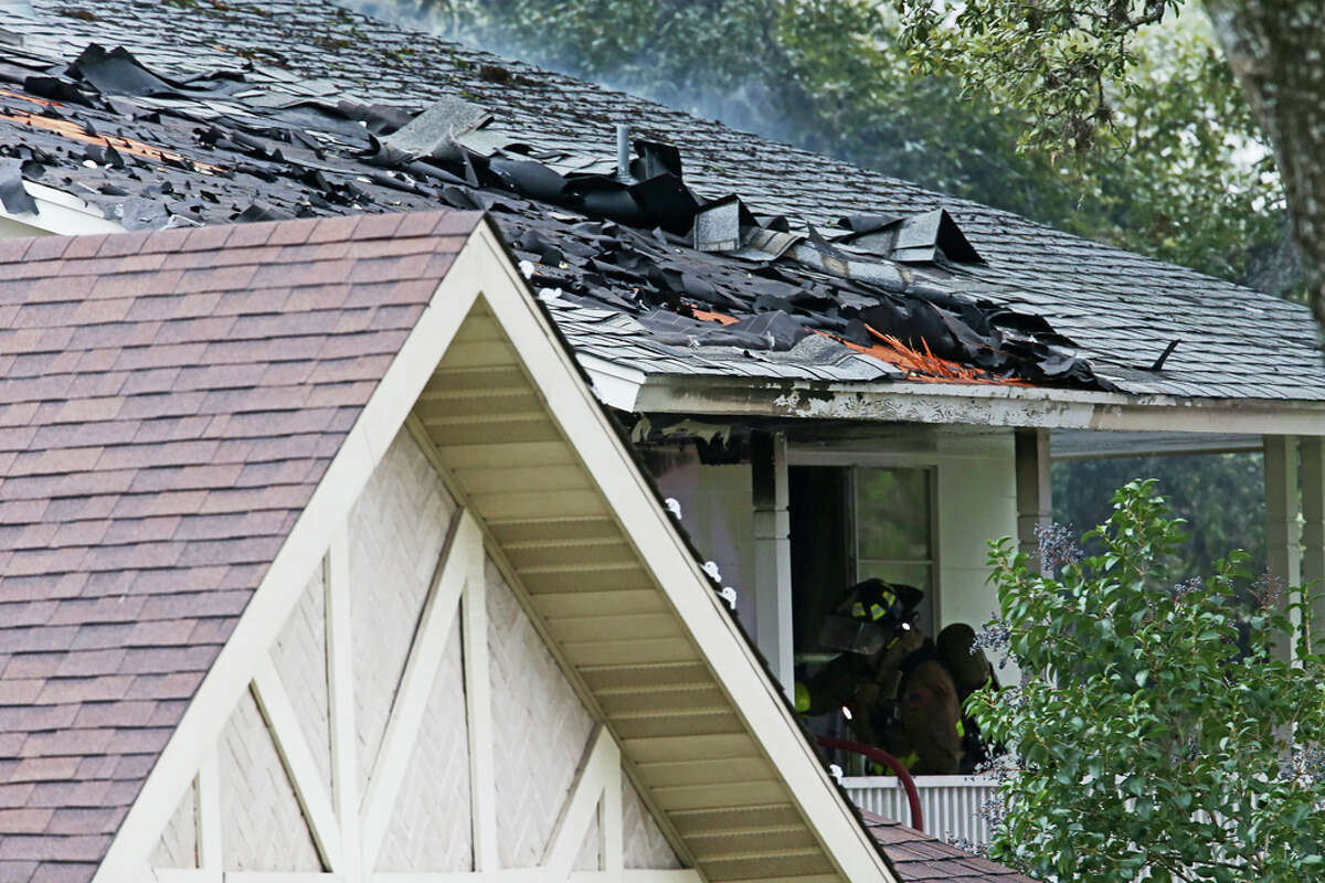 A firefighter is seen on the second floor of a house on the 3400 block of Stonehaven Road, Wednesday, Feb. 19, 2020. According to San Antonio Police Chief William McManus, a man 29-year-old male barricaded himself in the house after they responded to a vehicle fire at the scene. His body was later found on the second floor.