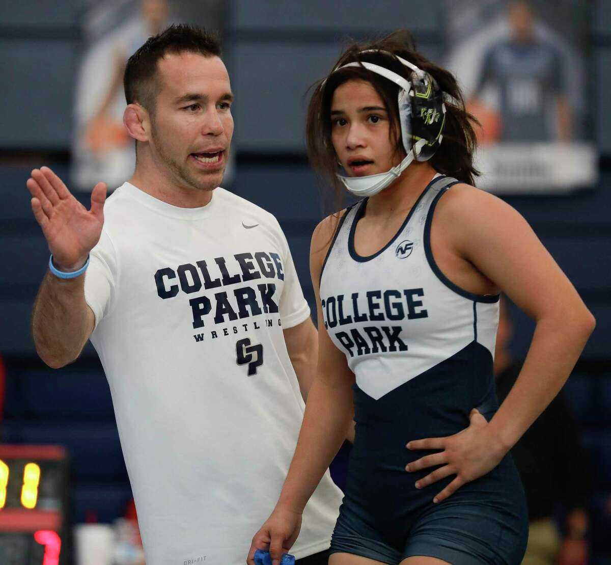 College Park head coach Erik Spjut talks with Jayden Bazemore during a break in a 119-pound championship bout at the District 8-6A wrestling championships at Bryan High School, Thursday, Feb. 6, 2020, in Bryan.