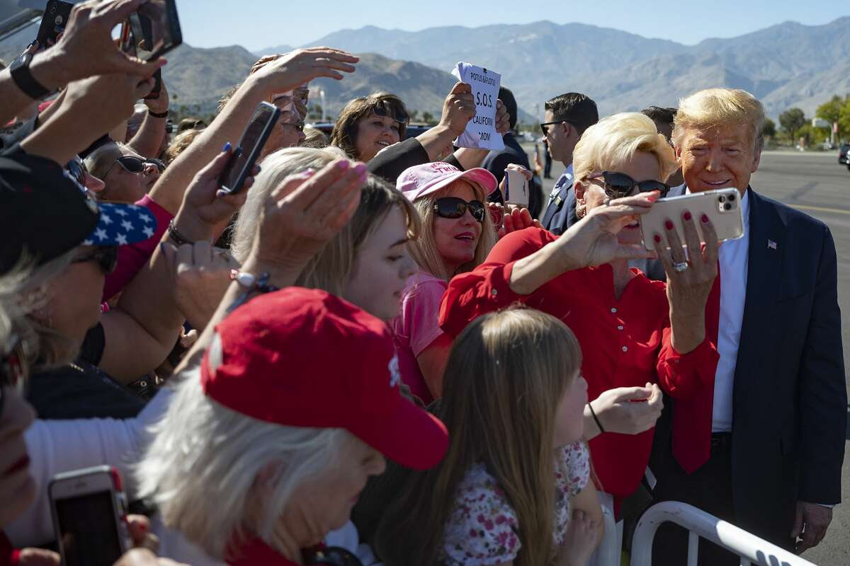 US President Donald Trump takes selfies with supporters as he arrives in Palm Springs, California, on February 19, 2020.