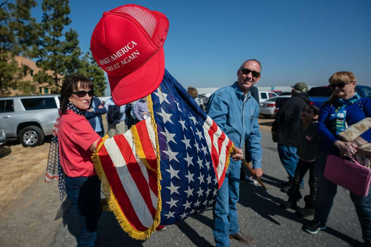 BUTTONWILLOW, CA--James Morrison waves a flag as he waits in line to attend President Trump's visit to Bakersfield on Wednesday, Feb 19, 2020.