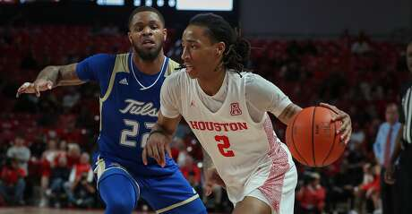 Houston Cougars guard Caleb Mills (2) drives around Tulsa Golden Hurricane guard Reggie Jones (22) during the first half of an NCAA basketball game at Fertitta Center Wednesday, Feb. 19, 2020, in Houston.