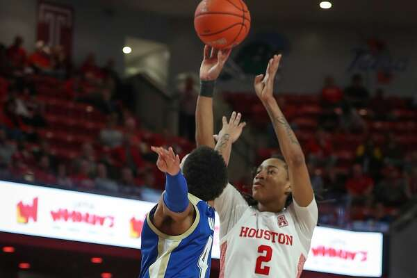 Houston Cougars guard Caleb Mills (2) gets a shot over Tulsa Golden Hurricane guard Isaiah Hill (4) during the second half of an NCAA basketball game at Fertitta Center Wednesday, Feb. 19, 2020, in Houston.