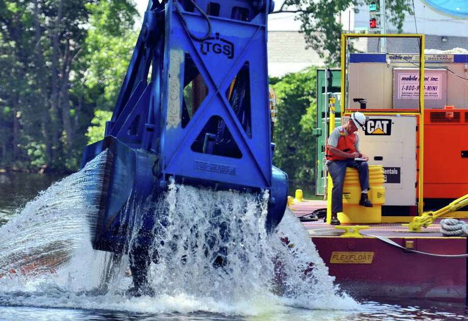 In this Aug. 11, 2010, a worker observes a crane remove a load onto an adjacent barge as dredging operations resumed in the Yacht Basin section of Fort Edward, NY. (Philip Kamrass / Times Union archive)