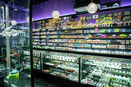 E-cigarette devices and juice for devices that have their own refillable tanks fill shelves at the Vapor Trend Vape & CBD Shop along Heights Boulevard at the Katy Freeway in Houston, Monday, Jan. 6, 2020. None of the products seen will be affected by the coming federal ban on flavored e-cigarette cartridges.