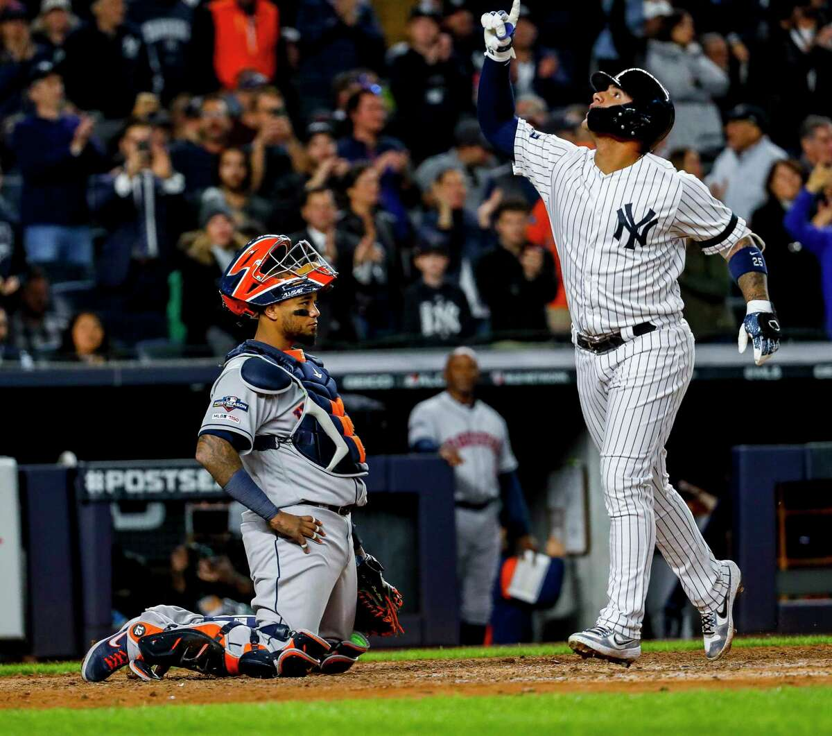 Houston Astros catcher Martin Maldonado (12) watches as New York Yankees second baseman Gleyber Torres (25) crosses home plate after hitting a solo home run during the eighth inning of Game 3 of the American League Championship Series at Yankee Stadium in New York on Tuesday, Oct. 15, 2019.