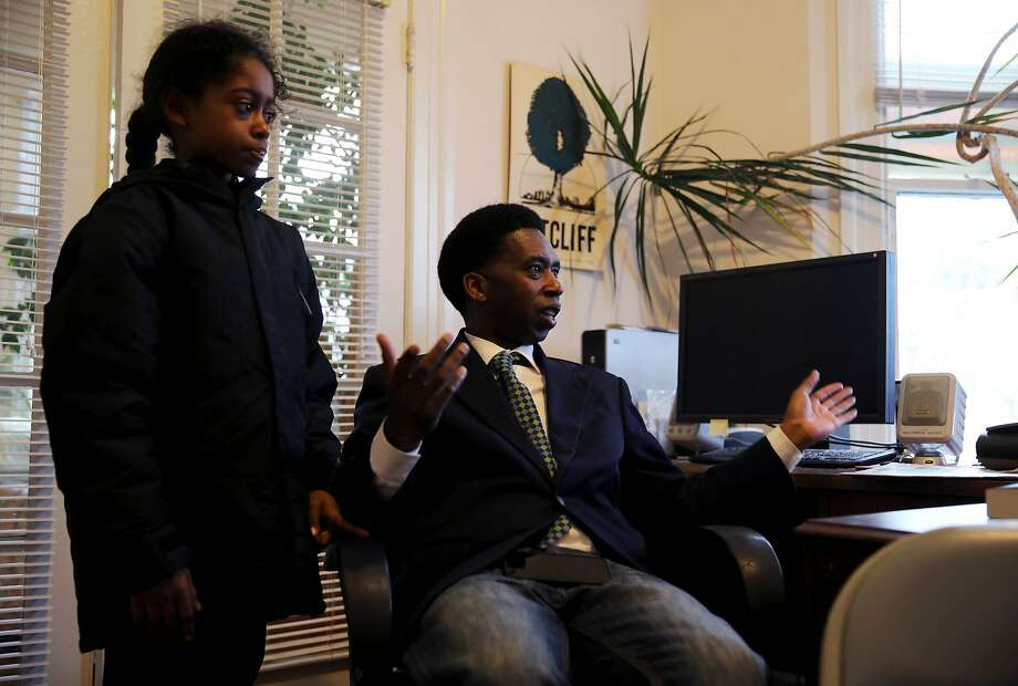 Kamari Epps, 9 (left), stands beside his father, S.F. documentary filmmaker Kevin Epps, who faces a murder charge, as Kevin speaks with Willie Ratcliff, publisher of the San Francisco Bay View, in Ratcliff's office. Photo: Yalonda M. James / The Chronicle