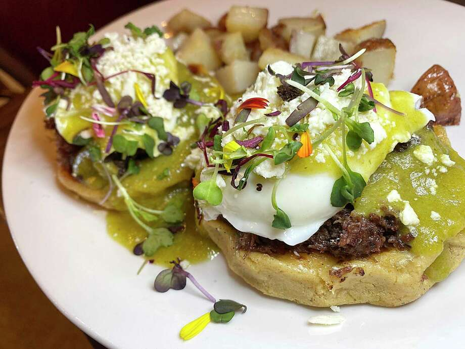 Mexican Benedicts include barbacoa, poached eggs, green chile hollandaise, queso fresco and cilantro on handmade corn sopes with a side of rosemary potatoes at Marla Restaurant. Photo: Mike Sutter /Staff