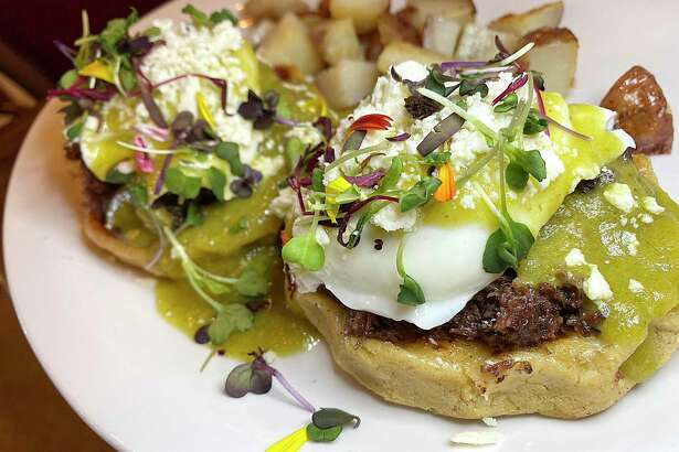 Mexican Benedicts include barbacoa, poached eggs, green chile hollandaise, queso fresco and cilantro on handmade corn sopes with a side of rosemary potatoes at Marla Restaurant.