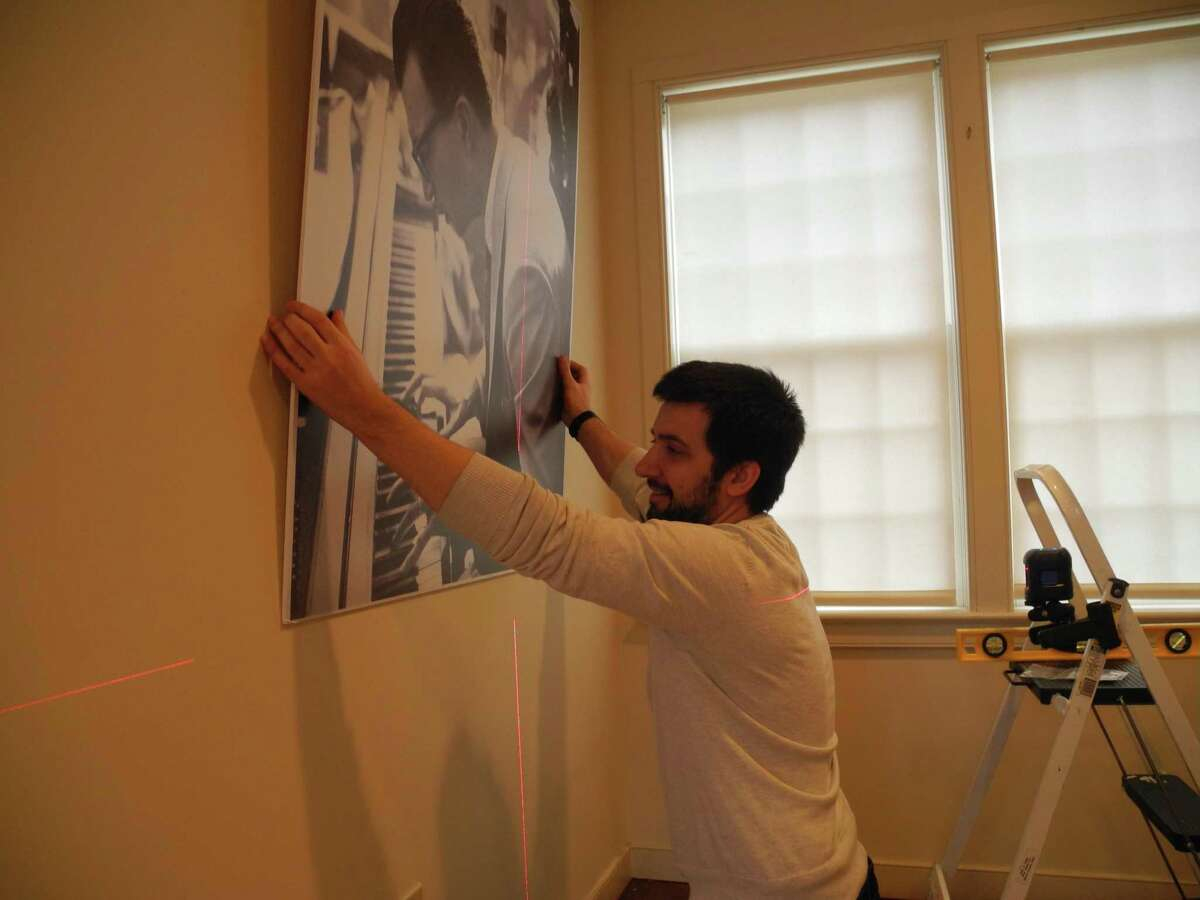 Associate Curator Nick Foster hangs a photo of Dave Brubeck for the Wilton Historical Society's upcoming exhibition, Remembering Dave: A Brubeck Family Album, opening Feb. 21.