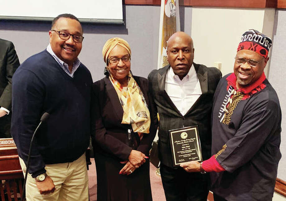 "Steve Gray, third from left, accepts a Madison County Living Legend Community Service Award on behalf of his mother, Vera Gray, of Alton. Also pictured are Madison County Board members Victor Valentine, Gussie Glasper and Michael ""Doc"" Holliday."