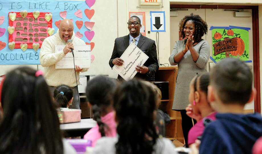 Stamford's NAACP president Guy Fortt and Rev. Robert Jackson of Bethel A.M.E. Church present a check in the amount of $2,200 to Roxbury Elementary School to cover the cost of the outstanding lunch debt for the entire school during student lunch on Feb. 19, 2020 in Stamford, Connecticut. At right is co-principal Edith Presley, who accepted the checks on behave of the school. Photo: Matthew Brown / Hearst Connecticut Media / Stamford Advocate