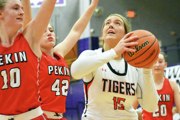 Edwardsville forward Kylie Burg looks to put up a shot over two Pekin defenders in the second quarter of Wednesday's Class 4A Collinsville Regional semifinal game in Collinsville.