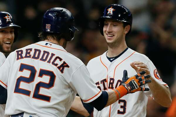 Kyle Tucker #3 of the Houston Astros is congratulated by Josh Reddick #22 and George Springer #4 as he scores in the eighth inning against the Los Angeles Angels of Anaheim at Minute Maid Park on September 22, 2018 in Houston, Texas.