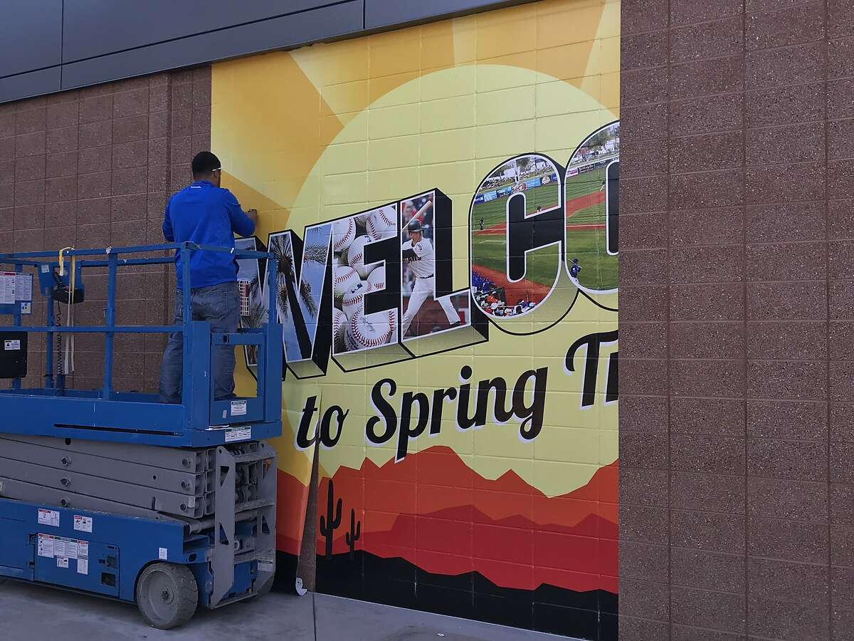 """Sign-company worker Nestor Aguilar prepares a """"Welcome to Scottsdale"""" banner inside Scottsdale Stadium. The Cactus League is scheduled to begin Saturday."""