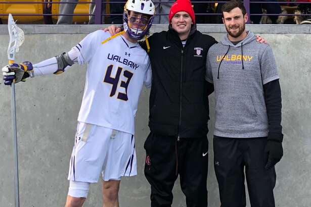 Cornell lacrosse's Ryan Maloney, middle, poses with cousin Tanner Hay, left, a UAlbany defenseman, and brother John, a UAlbany assistant coach, during a game on Feb. 15, 2020. (John Maloney)