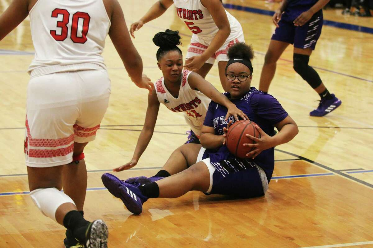 Senior Thailynn Grays ends up on the floor after scrambling for the ball before tossing the ball to her teammate Tuesday night at Baytown Sterling High School gym in the first round of the playoffs.