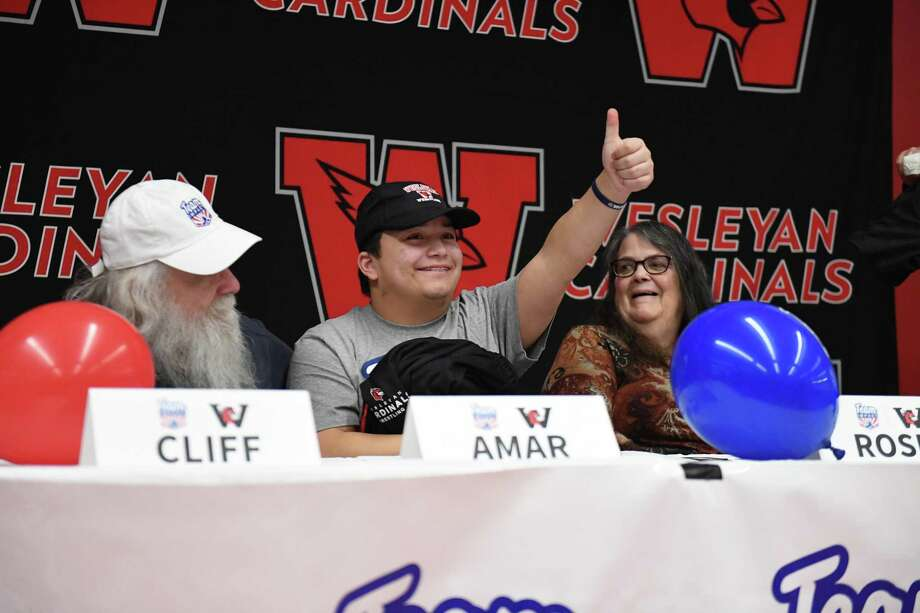 The Wesleyan University wrestling team added its newest member last week when 14-year old Amar Champlin, 14, center, of Team IMPACT signed his national letter of intent. Photo: Bre Cavanaugh Photo