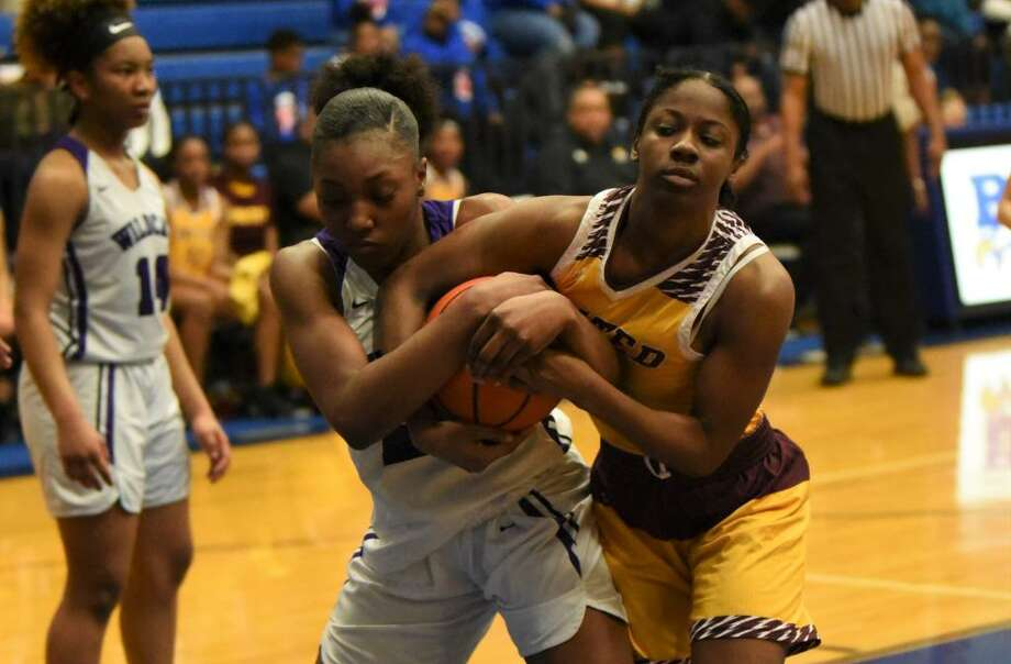 Humble's Jashya Wortham (left) fights for a rebound in the Lady Wildcats' bi-district playoff game against Beaumont United. Photo: Contributed Photo
