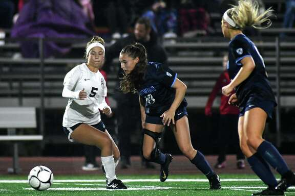 Kingwood junior Cadyn Hulse, center, works the ball past Atascocita's Victoria Arenivas (5) during the first period of their district matchup at KHS on Feb. 19, 2020.