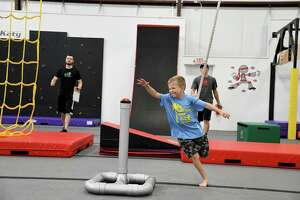 A student rejoices as he hits the buzzer after making it up the wall at USA Ninja Challenge Katy.