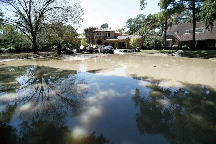 Flood water remains at the end of a cul-de-sac in the Memorial Glen subdivision, west of Beltway 8, near Memorial and Wilchester, Friday, Sept. 8, 2017, in Houston. As people in homes in that area were finally able to start working on cleaning up the mess left behind after their homes were flooded for more than a week after Hurricane Harvey.