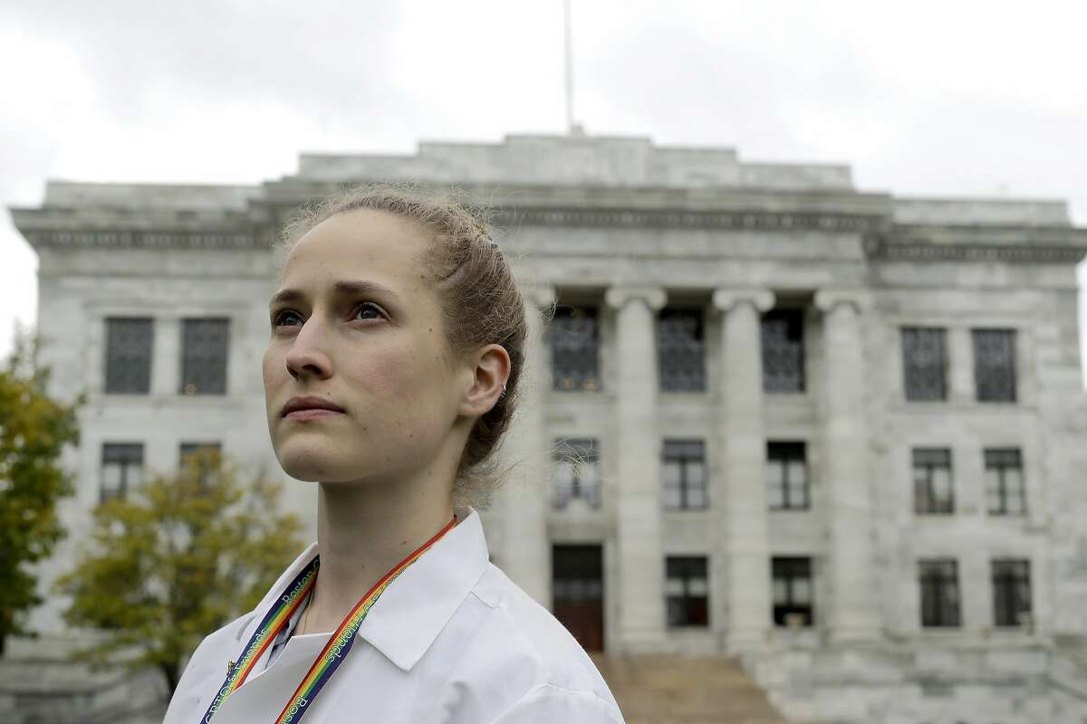 In this Thursday, Oct. 17, 2019 photo Harvard Medical School student Aliya Feroe, of Minneapolis, Minn., poses for a photograph on the school's campus, in Boston. Feroe recalls a flustered OB-GYN who referred her to another physician after learning she identified as queer. Medical schools are beefing up education on LBGTQ health issues. And some schools are making a big push to recruit LGBTQ medical students, backed by research showing that patients often get better care when treated by doctors who are more like them. (AP Photo/Steven Senne)