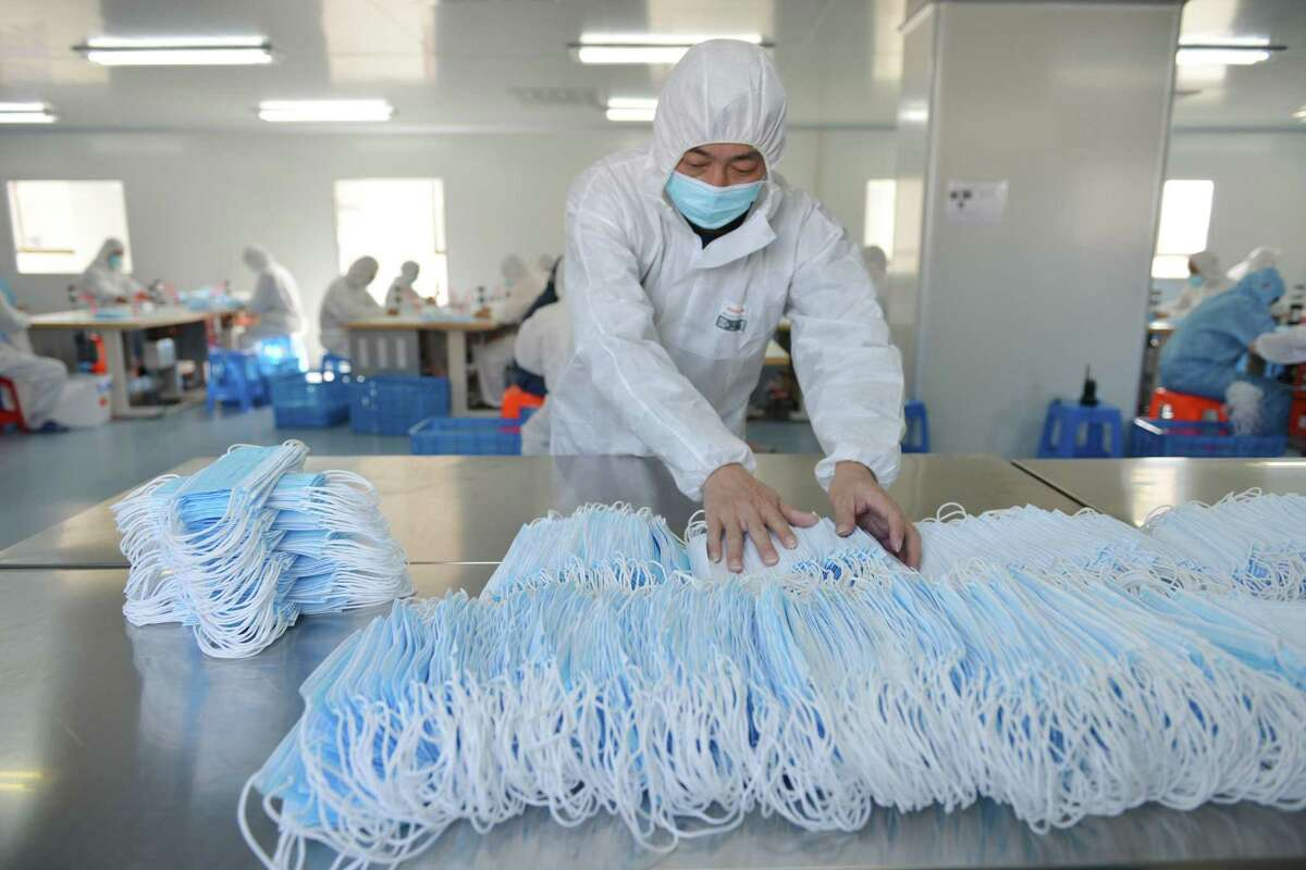 This photo taken on February 18, 2020 shows a worker sorting face masks being produced to satisfy increased demand during China's COVID-19 coronavirus outbreak, at a factory in Nanjing, in China's Jiangsu province. - The medical equipment factory switched surgical instruments and dental equipment production lines to a mask production line to meet the increased demand. (Photo by STR / AFP) / China OUT (Photo by STR/AFP via Getty Images)
