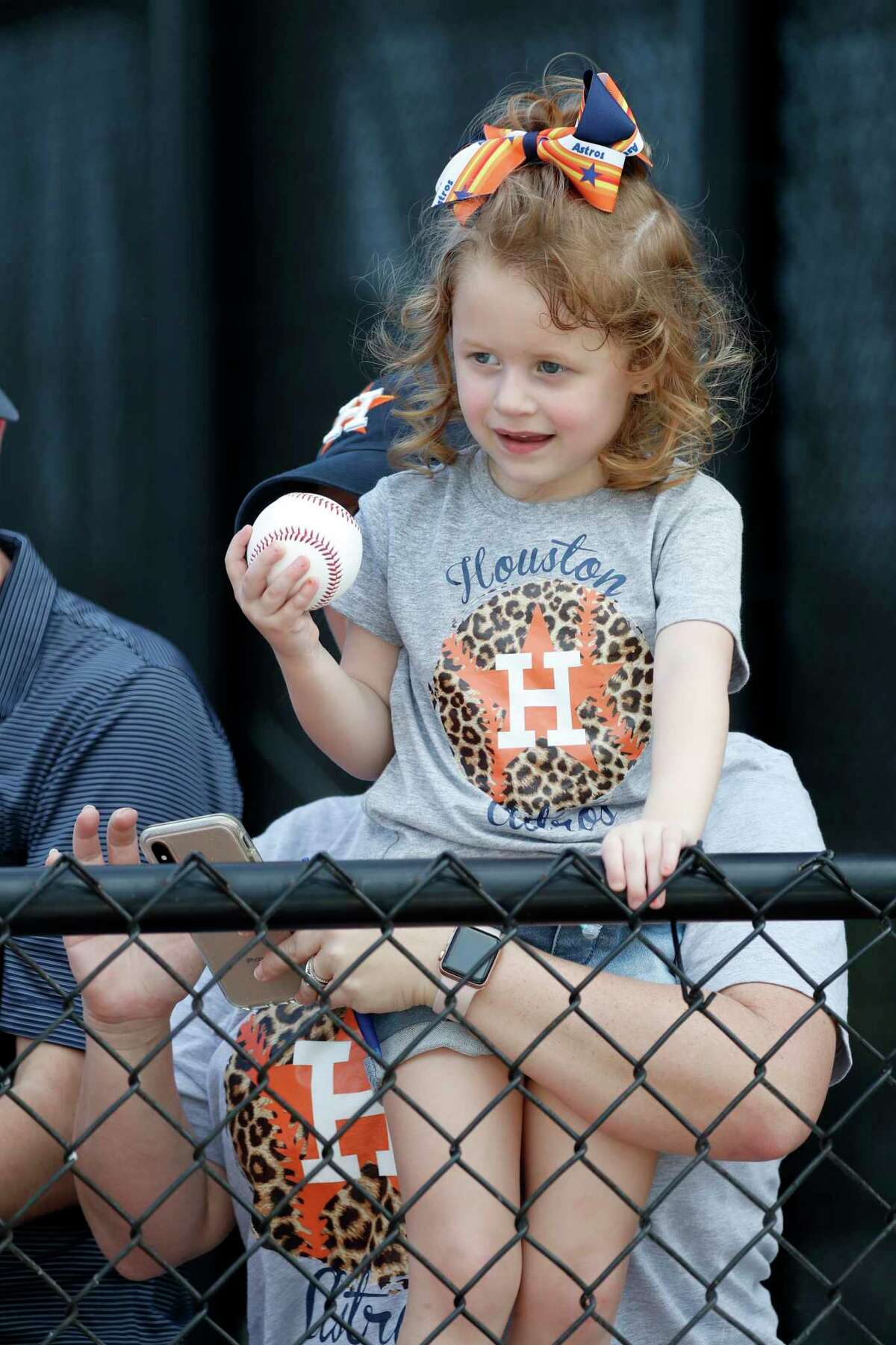 Harper Wleczyk, 3, of Houston, waits for players to sigh her baseball during the Houston Astros spring training workouts at the Fitteam Ballpark of The Palm Beaches, in West Palm Beach , Thursday, Feb. 20, 2020.