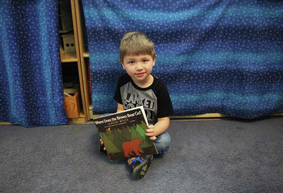 Huron ISD student Tanner Spencer enjoys looking at pictures in his book. (Sara Eisinger/ Huron Daily Tribune)