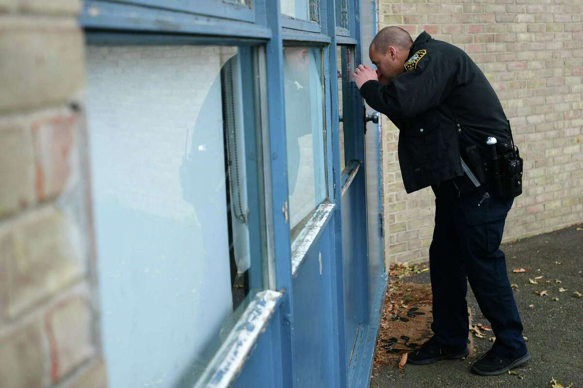 School Resource officer Neal Robertson and Naramake Elementary School staff work through the school make sure doors are locked and blinds closed and staff and students shelter in place during a lockdown drill Nov. 22 at the school in Norwalk.