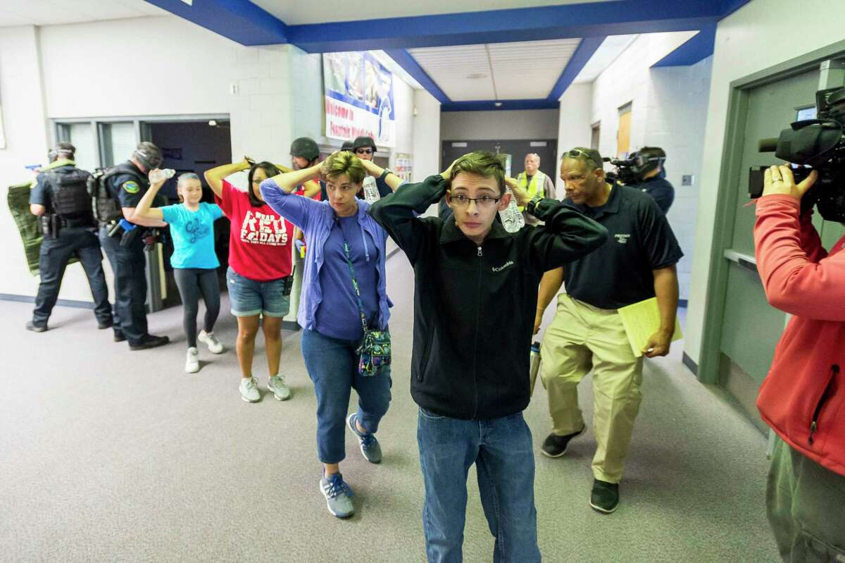 Students are led out of school as members of the Fountain Police Department take part in an Active Shooter Response Training exercise at Fountain Middle School in Fountain, Colo., June 9, 2017. The nation's two largest teachers unions want schools to revise or eliminate active shooter drills, asserting that they can harm students' mental health and that there are better ways to prepare for the possibility of a school shooting.