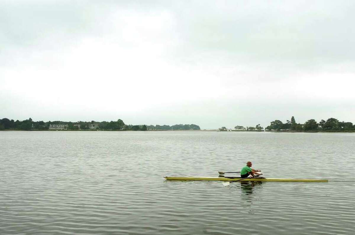 Rob Slocum rows in Holly Pond behind his home in Stamford, Conn. on Monday August 16, 2010.