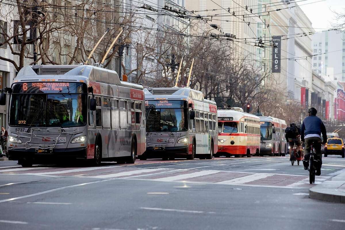 Cyclists move past a row of Muni buses and street cars lined up on Market Street in San Francisco, Calif. Wednesday, January 29, 2020. Beginning January 29, private vehicles will be banned from driving along Market Street between Steuart and 10th streets, leaving it free for cyclists, pedestrians and public transit vehicles.