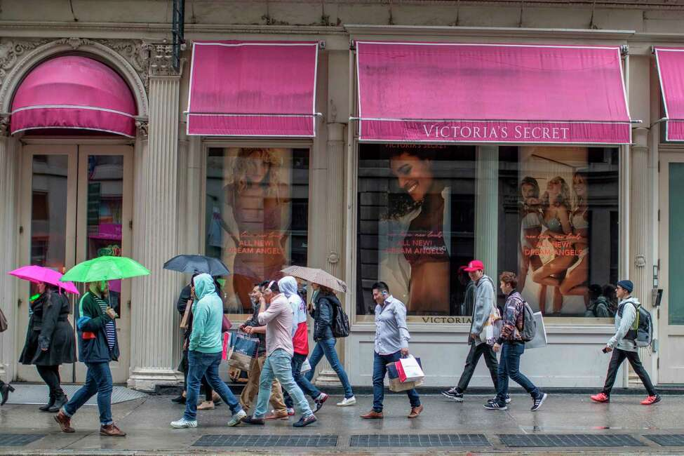 FILE- In this April 4, 2018, file photo, shoppers walk past the Victoria's Secret store on Broadway in the Soho neighborhood of New York. Victoria's Secret's owner, L Brands, said that the private-equity firm Sycamore Brands will buy 55% of Victoria's Secret for about $525 million. Victoria's Secret will become a private company. (AP Photo/Mary Altaffer, File)