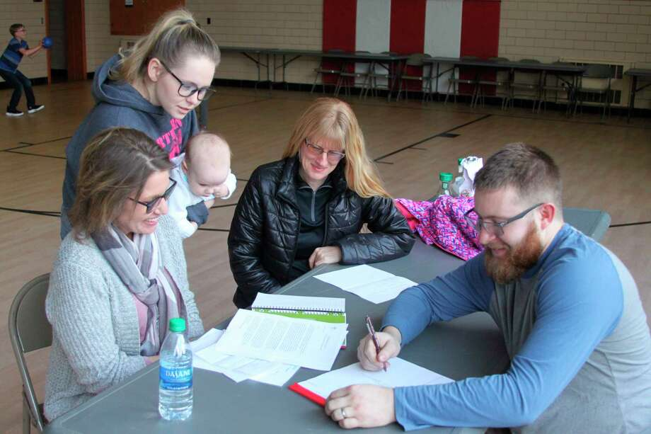 Members of the Trinity Lutheran Church Roast Pork and Sauerkraut Supper make plans for the upcoming event that will take place from 5-7 p.m. on March 14. Pictured (left to right) are Melissa Gentz,  Michaela Guerra, Sky Mage and Greg Staffeld making plans for the event. (Ken Grabowski/News Advocate)