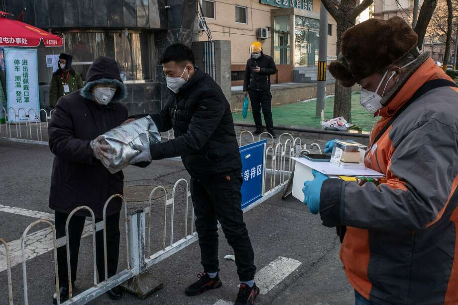 Deliveries are made to a checkpoint outside a building in Beijing, offering a lifeline to residents. Photo: Gilles Sabrie / New York Times