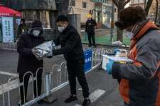 Deliveries are made to a checkpoint outside a building in Beijing, Tuesday, Feb. 18, 2020. Delivery drivers across China offer a lifeline to millions of people barricaded in their homes during the coronavirus outbreak, but the work puts them at risk. (Gilles Sabrie/The New York Times)