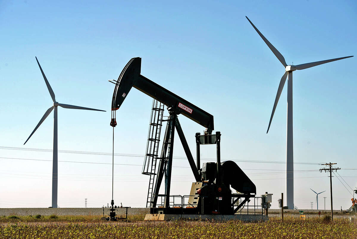A pumping unit stands between two wind turbines north of Stanton in this 2015 file photo. Consulting company Deloitte says oil and gas companies are facing a choice between how much to invest in oil and gas and how much to invest in low-carbon energy sources.