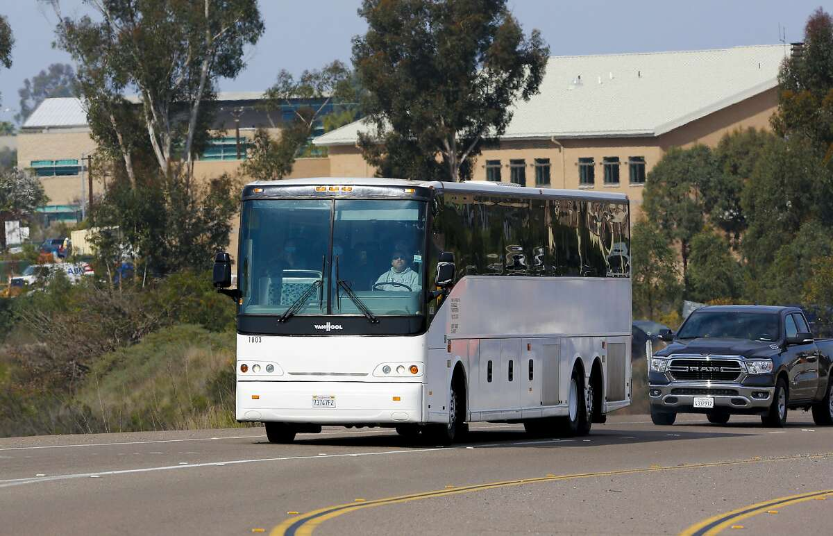A bus transporting passengers that were temporary quarantined at Marine Corps Air Station Miramar, Calif., leave the base enroute to public transportation terminal locations in San Diego, Tuesday, Feb. 18, 2020. Nearly 350 Americans who fled the coronavirus zone in China completed a 14-day quarantine at California military bases and were cleared to go home Tuesday, officials announced. (Nelvin C. Cepeda/The San Diego Union-Tribune via AP)