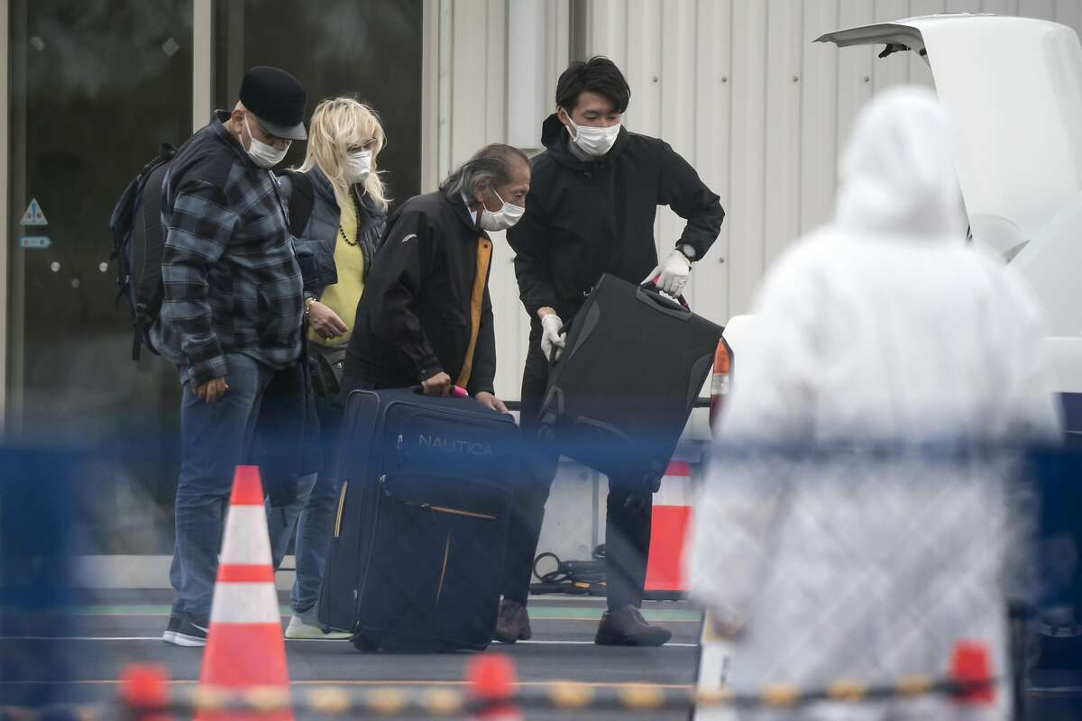 YOKOHAMA, JAPAN - FEBRUARY 20: Passengers are assisted while loading bags into a taxi after disembarking from the quarantined Diamond Princess cruise ship, docked at the Daikoku Pier on February 20, 2020 in Yokohama, Japan. Passengers who have tested negative for the coronavirus (COVID-19) have been disembarking the cruise ship since Wednesday, as at least 621 passengers and crew onboard have tested positive for the coronavirus (COVID-19). Including cases onboard the ship, 705 people in Japan have now been diagnosed with COVID-19, making it the worst affected country outside of China. (Photo by Tomohiro Ohsumi/Getty Images) *** BESTPIX ***