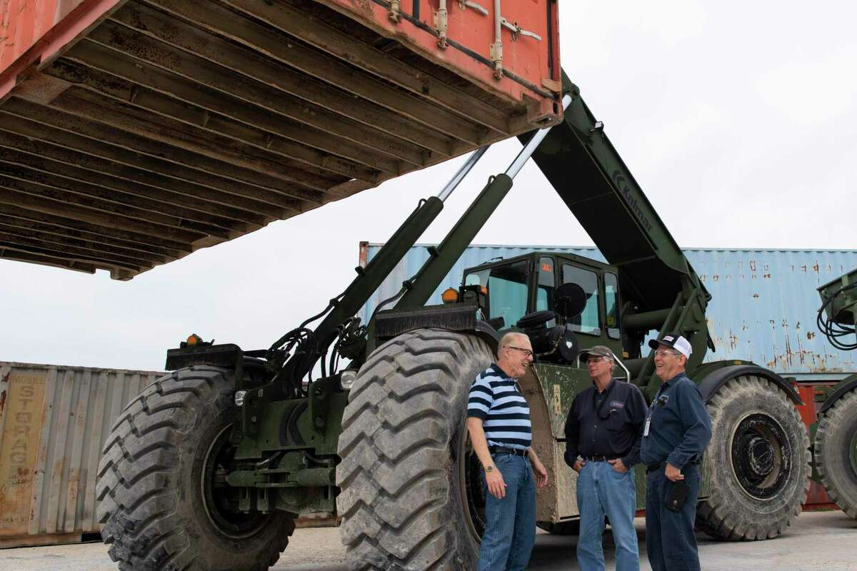 Stephen M. Speakes, left, CEO and president of the Independent Rough Terrain Center in Cibolo, speaks with Steve Stephens and George Deck by a vehicle called the Rough Terrain Container Handler, or RTCH.