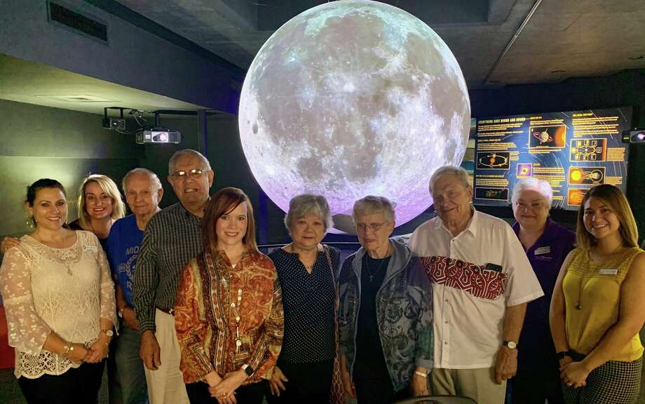 Tracy Renton and Kathleen Kirwan-Haynie, far left, stand with RSVP volunteers and Museum of the Southwest staff in an outing to Science on a Sphere.