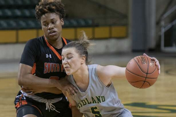 Midland College's Grace Beasley drives to the basket as South Plains' Asia McCoy tries to defend 02/20/19 at the Chaparral Center. Tim Fischer/Reporter-Telegram