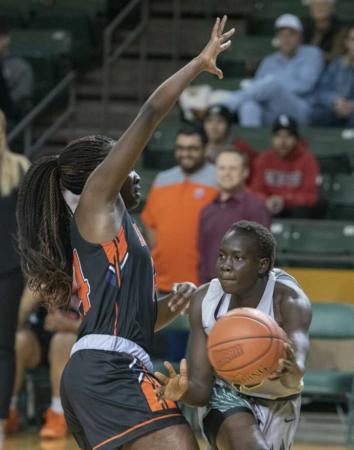 Midland College's Nyaduoth Lok looks to pass around South Plains' Sarah Shematsi 02/20/19 at the Chaparral Center. Tim Fischer/Reporter-Telegram Photo: Tim Fischer/Midland Reporter-Telegram